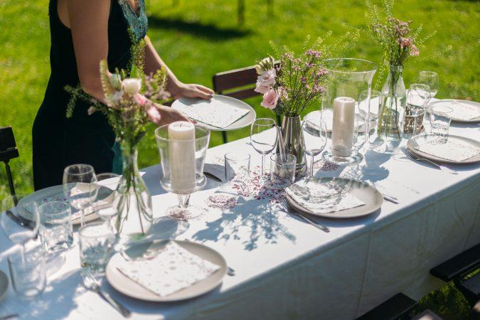 Frau deckt den Tisch im Freien zum Mittagessen