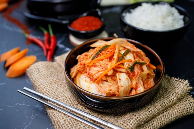 Koreanisches Kimchi in einer Schüssel auf grauem Steinuntergrund