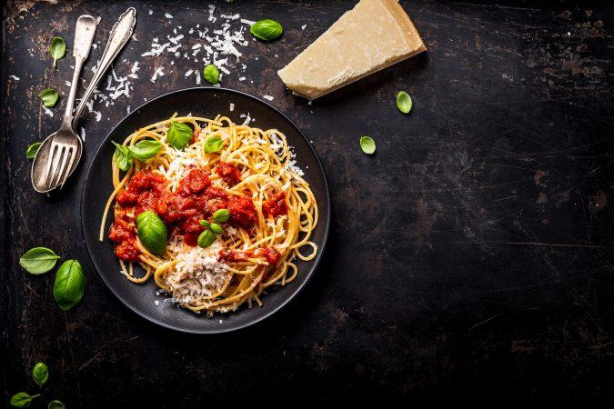 Frischer Parmesan auf Spagetti mit Basilikum auf einer dunklen Steinarbeitsplatte