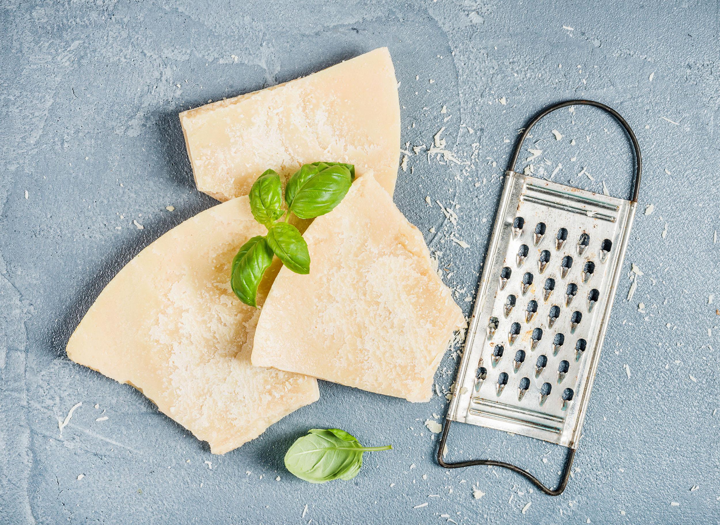 Scheiben von Parmesan Käse auf einer hellgrauen Steinplatte