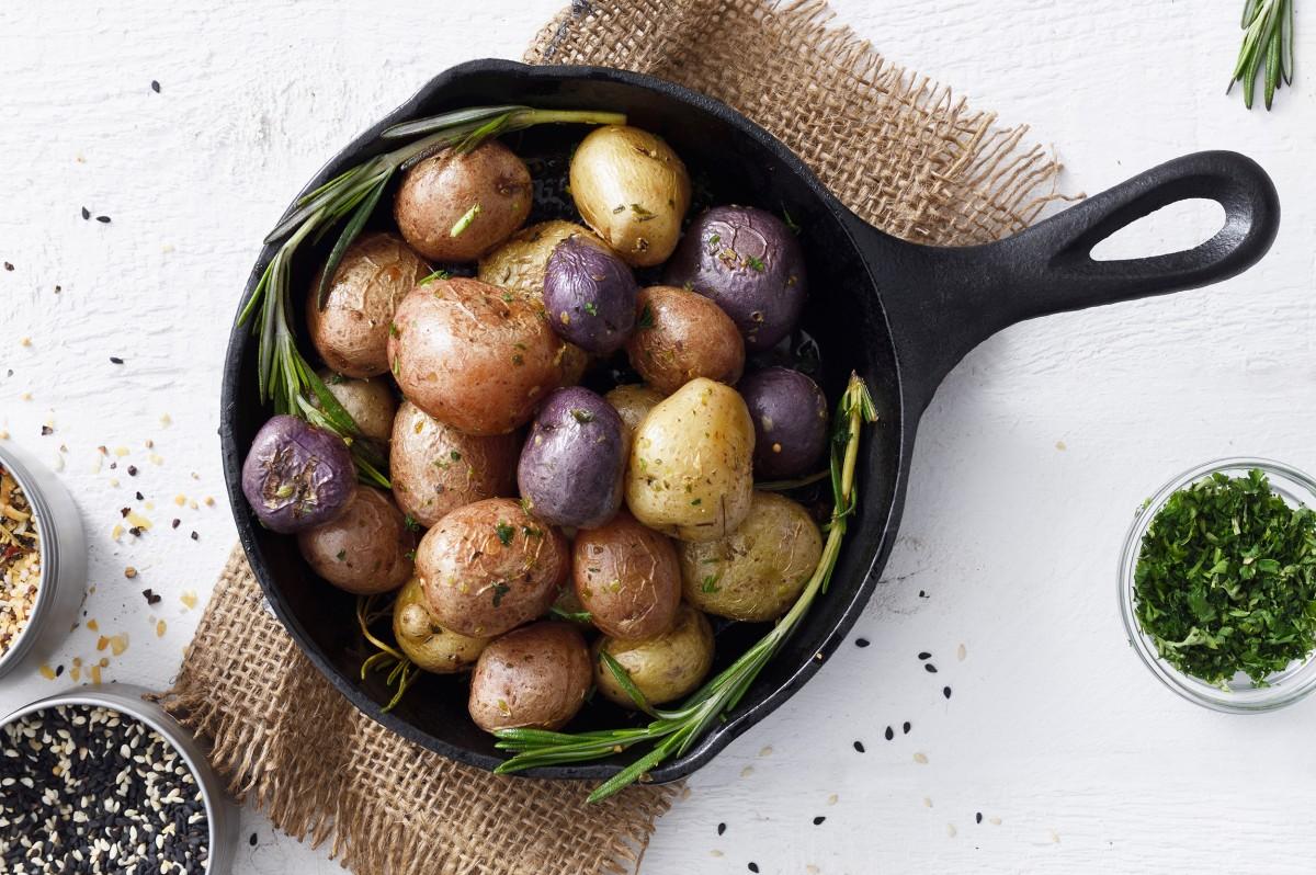 Kartoffeln in einer gusseisernen Pfanne auf einem hellen Steinuntergrund