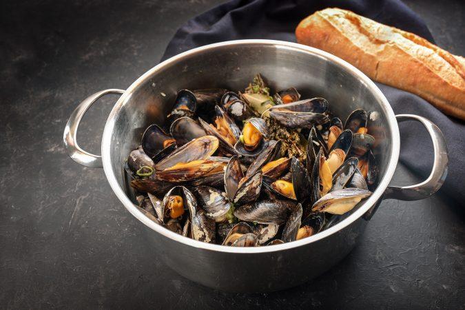 Frisch gekochte Muscheln in einem Topf auf einer grauen Steinplatte