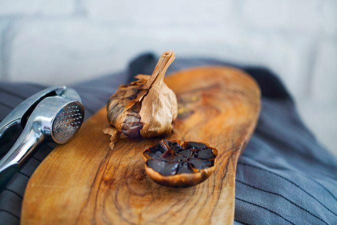 Schwarzer Knoblauch als aufgeschnittene Knolle auf einem Holzbrett